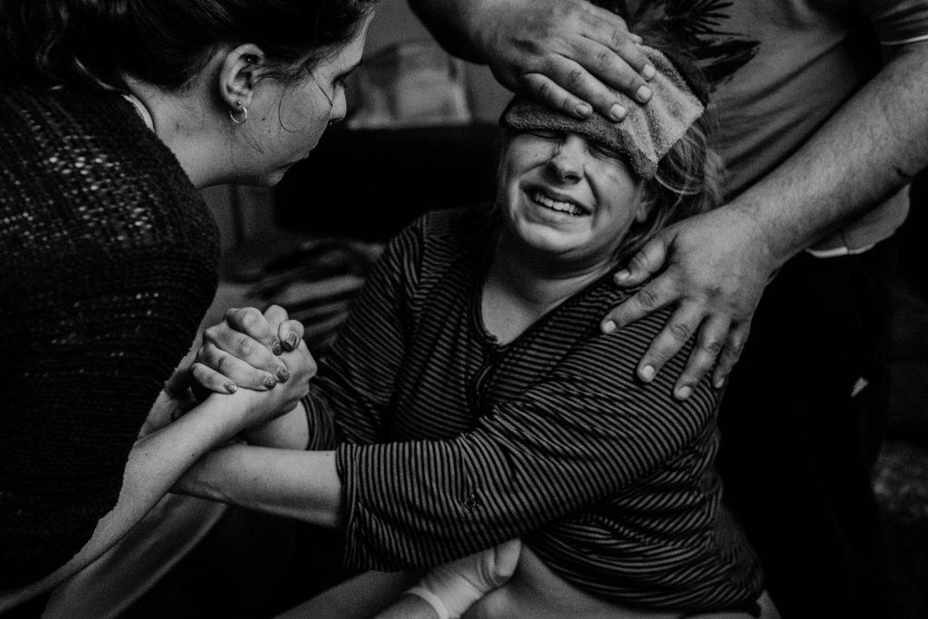 Gebärende Frau sitzt auf dem Geburtshocker, sie befindet sich in der letzten Phase der Geburt, was sich an ihrem Gesichtsausdruck erkennen lässt. Der Kindsvater steht hinter ihr und hält ihr einen kalten Waschlappen an die Stirn, seine andere Hand liegt auf ihrer Schulter. Die Hebammenschülerin spricht beruhigend zur Gebärenden. Diese hält sich an ihren Händen fest.